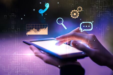 Close up of female hands using tablet with business interface on blurry background. Communication and finance concept. Double exposure