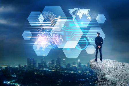 Back view of young businessman on mountain top looking at abstract circuit brain interface on blurry illuminated night city background. Artificial intelligence and mind concept. Double exposure