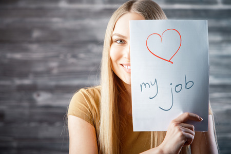 Attractive young woman with love my job text on wooden background. Success and occupation concept