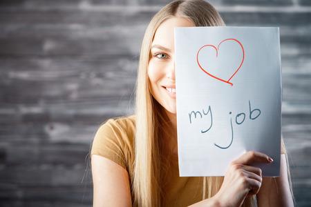Attraktive junge Frau mit der Liebe meinen Job Text auf hölzernem Hintergrund . Erfolg und Beruf Konzept