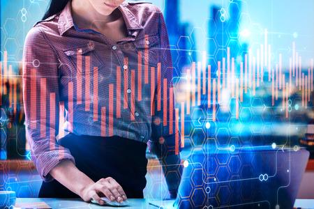 Geschäftsfrau Hände mit Laptop am modernen Büro Desktop mit Lieferungen und abstrakte Stadt Panel . Buchhaltung und Gewinn Konzept . Doppelbelichtung