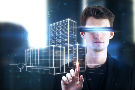 Portrait of handsome young european businessman with virtual reality glasses pointing at city sketch. Future and engineering concept. Double exposure  Stock Photo