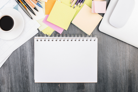 Top view of modern desktop with empty spiral notepad, other objects and supplies. Paperwork, finance, sketch concept. Mock up