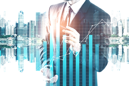 Businessman drawing abstract business chart hologram on city background. Future, innovation and finance concept. Double exposure