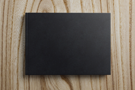 Top view and close up of empty black book on wooden background. Advertising, media and message concept. Mock up, 3D Rendering