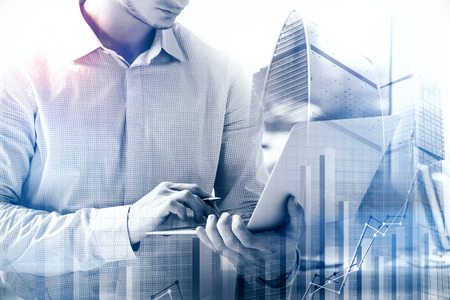 Businessan using laptop with business chart on abstract toned city background. Finance and banking concept. Double exposure