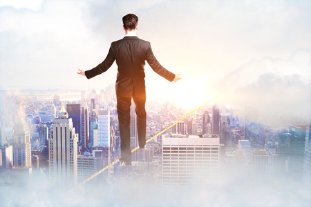 Back view of young businessman walking on rope in sky. City background. Success and balancing concept