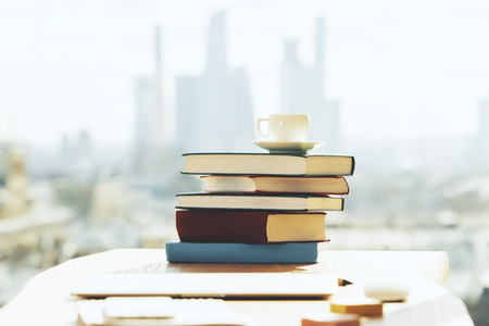 Close up of workplace with book stack and coffee cup on blurry city background with sunlight. Education, morning, breakfast and leisure concept Stock Photo