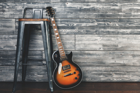Guitar and chair in wooden interior/studio. Music, leisure, rehearsal and lifestyle concept