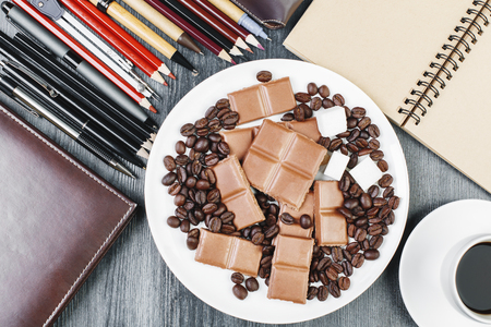 Top view of plate with chocolate and coffee on wooden desk with supplies. Treats and sweets concept