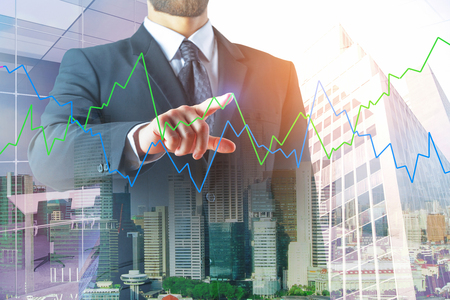 Investment and monitoring concept. Thoughtful european businessman with abstract forex chart on bright city background. Double exposure
