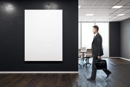 Uomo d'affari che cammina nell'interno moderno dell'auditorium con il manifesto vuoto. Mock up, rendering 3D