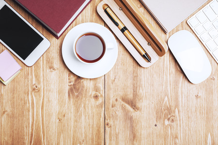 Top view of wooden office desktop with empty device, supplies and copy space. Occupation and lifestyle concept Stock Photo