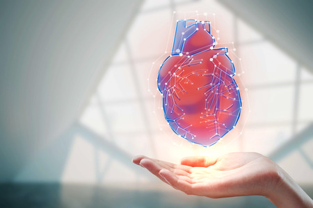 Female hand holding abstract heart hologram on blurry interior background. Medicine, cardiology and innovation concept. Double exposure  Stok Fotoğraf