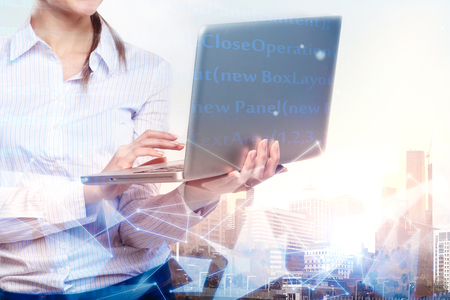 Businesswoman hands using laptop computer on abstract city background with glowing digtal interface. Future and technology concept. Double exposure