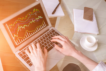 Close up of female hands using laptop with forex chart at modern office desk with items. Filtered image. Accounting and finance concept  Standard-Bild