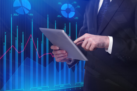 Businessman using tablet on abstract blue forex chart background. Investment and analysis concept   Standard-Bild