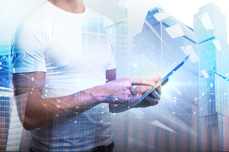 Man using tablet with forex chart on abstract city background. Technology and finance concept. Double exposure