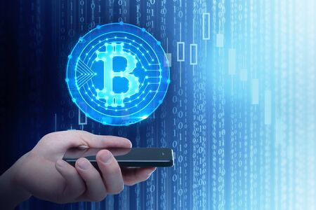 Hand holding smartphone with creative bitcoin hologram on blue binary code background. Cryptocurrency and computing concept. Double exposure