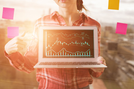 Unrecognizable businesswoman pointing at laptop with business chart on blurry city background with stickers. Presentation and finance concept. Toned image  Standard-Bild