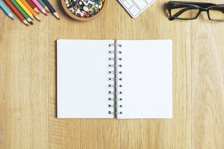Top view of empty notepad on wooden office workplace with other supplies. Mock up