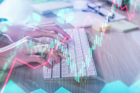 Accounting and technology concept. Hands using keyboard with forex chart placed on office desk with supplies and other items. Double exposure