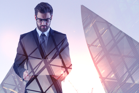 Businessman using laptop on abstract city background with sunlight. Technology and communication concept. Double exposure