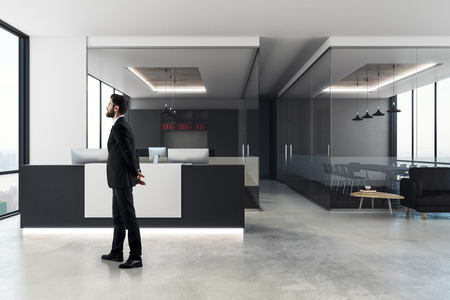 Thoughtful businessman standing in modern office interior with reception desk, city view and daylight. 3D Rendering