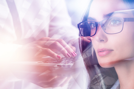 Attractive european businesswoman in glasses typing on laptop keyboard. Technology and communication concept. Double exposure