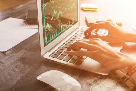 Close up of female hands using laptop with forex chart at modern office desk with items. Filtered image. Trade and finance concept  Standard-Bild