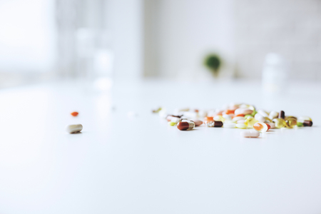 Close up of blurry white desktop with pills and tablets. Medicine and dose concept