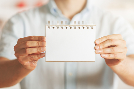 Businessman holding empty spiral notepad on blurry interior background. Mock up and presentation concept