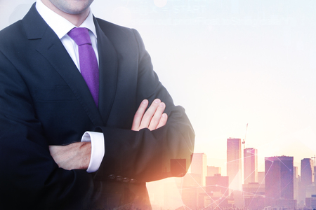 Success and tomorrow concept. Thoughtful businessman with folded arms on abstract city background. Double exposure