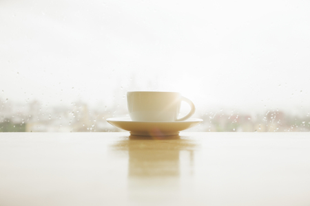 Coffee cup placed on white windowsill with reflection. Window with rainy blurry morning city view in the backgrouns. Autum or fall mood concept. Mock up