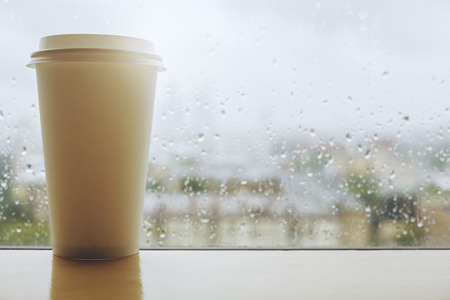 Take away coffee cup placed on white windowsill with reflection. Window with rainy blurry morning city view in the backgrouns. Autum or fall mood concept. Mock up  Stockfoto