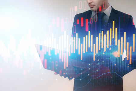 Side view of young businessman using laptop on abstract forex chart background. Technology and stock concept. Double exposure