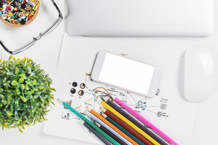 Mix of office supplies, laptop computer and mobile phone on stylish tabletop with other items. Above view. Mock up