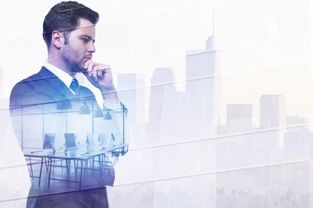 Attractive thoughtful young european businessman standing on abstract office city background with copy space. Success and job concept. Double exposure