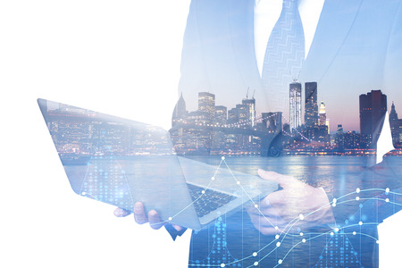 Side view of unrecognizable businessman using laptop on abstract city background with glowing forex chart. Technology, market and profit concept. Double exposure  Stock Photo