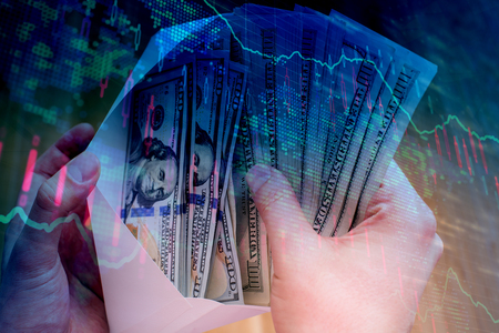 Male hand holding envelope with dollar bills on abstract forex background. Bribery and investment concept. Double exposure