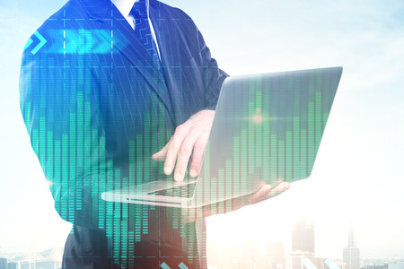 Unrecognizable european businessman using laptop on abstract creative city background with forex chart. Technology, communication and finance concept. Double exposure  Stock Photo