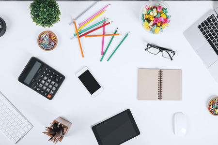 Close up of creative office desktop with empty tablet, smartphone and laptop, supplies and other items with copy space. Mock up, Above view