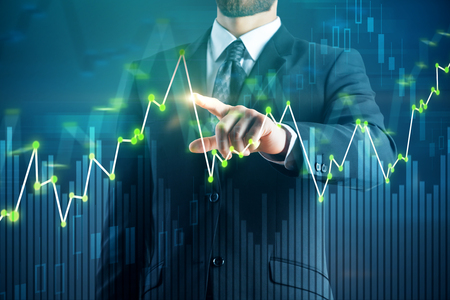 Businessman pointing at business chart on blurry background. Trade and management concept. Double exposure