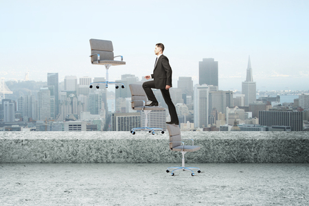 Businessman climbing abstract floating chairs on rooftop landscape background. Success and job concept