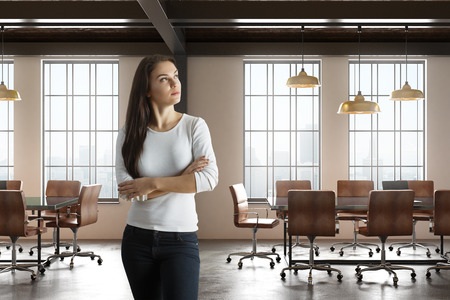 Attractive young woman with folded arms standing in modern conference room interior with city view and daylight. 3D Rendering
