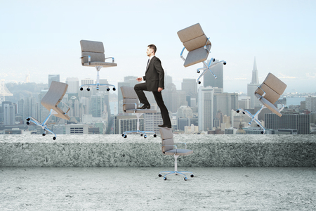 Businessman climbing abstract floating chairs on rooftop landscape background. Success and stepping concept Stock Photo