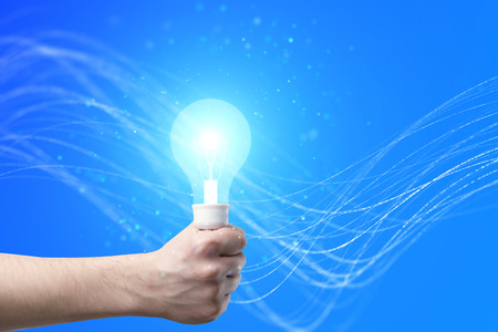 idea concept with hand holding luminious bulb in the center of abstract blue background. 3D render Stock Photo