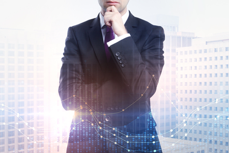 double exposure with thinking businessman in suit at city background and financial chart graphs
