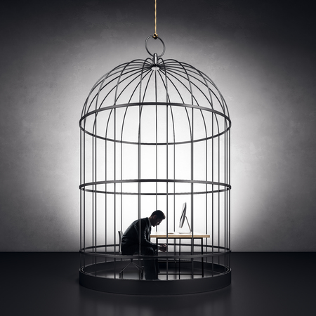 pondered businessman sitting by the worktop in metal birdcage at concrete wall background Фото со стока