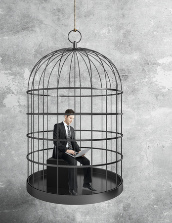 businessman working hard with laptop in birdcage on concrete wall background. Freedom and innovation concept